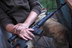 Soldathänder och slut för prickskyttgevär upp Kriga royaltyfri fotografi