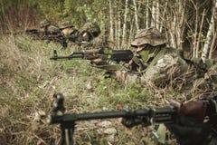 Soldati mascherati che preparano strategia militare Immagine Stock