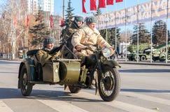Soldati sovietici con le armi sul vecchio motociclo dell'esercito fotografia stock