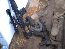 Soldatkängor, prickskyttgevär och nära övre för handeldvapen Kriga royaltyfri foto