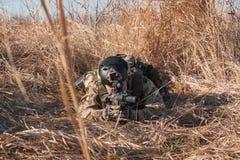 Soldatlüge in den Büschen mit Gewehr Stockfotos