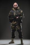 Soldatmann-Griff Maschinengewehr auf einem dunklen Hintergrund lizenzfreie stockbilder