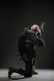 Soldatmann-Griff Maschinengewehr auf einem dunklen Hintergrund Lizenzfreie Stockfotografie