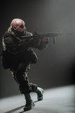 Soldatmann-Griff Maschinengewehr auf einem dunklen Hintergrund stockfotografie