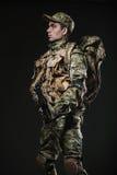 Soldatmann-Griff Maschinengewehr auf einem dunklen Hintergrund Stockfoto