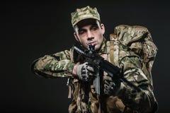 Soldatmann-Griff Maschinengewehr auf einem dunklen Hintergrund Lizenzfreie Stockfotos