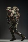 Soldatmann-Griff Maschinengewehr auf einem dunklen Hintergrund Stockbild