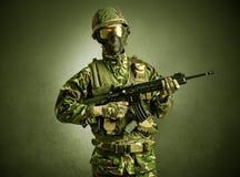 Soldatmedel i ett m?rkt utrymme med armar arkivbild