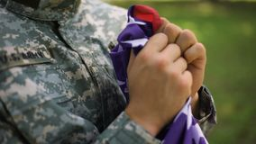 Soldato americano con la bandiera nazionale in mani, fiere di paese, festa dell'indipendenza archivi video