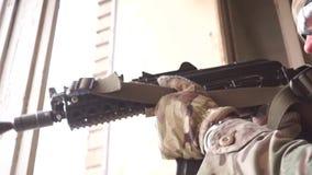 Soldato armato con un fucile di assalto che custodice stanza vicino alla finestra rotta video d archivio
