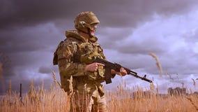 Soldato autentico in vestiti militari e casco che sta fermo e che gira intorno con la pistola in mani, perse in natura archivi video