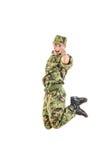 Soldato bello in uniforme verde e cappello del cammuffamento che saltano su Fotografia Stock