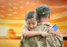 soldato che abbraccia figlia nel campo con la bandiera degli S.U.A. immagini stock