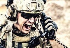 Soldato che comunica con il comando durante la battaglia Fotografia Stock