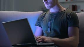 Soldato che lavora al computer portatile al sofà di seduta di notte, tecnologia moderna, guerra cyber stock footage