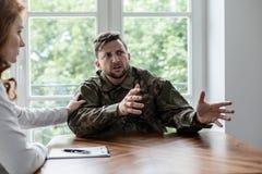 Soldato che parla della sua esperienza di guerra con timore Supporto di rappresentazione dello psichiatra fotografie stock