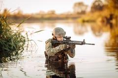Soldato che si muove attraverso l'acqua e che punta sul nemico fotografie stock
