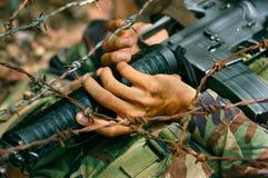 Soldato che striscia sotto la sbavatura Immagini Stock