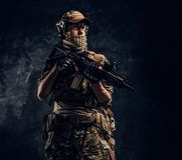 Soldato completamente attrezzato in uniforme del cammuffamento che tiene un fucile di assalto Foto dello studio contro una parete immagine stock