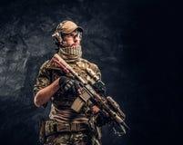 Soldato completamente attrezzato in uniforme del cammuffamento che tiene un fucile di assalto Foto dello studio contro una parete fotografia stock