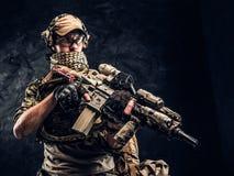 Soldato completamente attrezzato in uniforme del cammuffamento che tiene un fucile di assalto Foto dello studio contro una parete immagini stock