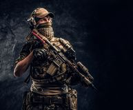 Soldato completamente attrezzato in uniforme del cammuffamento che tiene un fucile di assalto Foto dello studio contro una parete fotografia stock libera da diritti