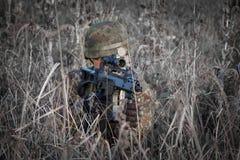 Soldato con il casco militare e pistola cammuffata nell'azione - spari da un nascondiglio il tiro fotografia stock