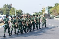 soldato con la lunga autonomia della pistola del fucile che sorveglia sulla città Gruppo di soldati che marciano sulla strada asf immagini stock