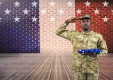 Soldato con la mano sulla testa che tiene una bandiera americana davanti alla bandiera del francese Immagini Stock Libere da Diritti
