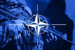 Soldato con la mitragliatrice con la bandiera della NATO Alliance Immagini Stock