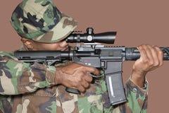Soldato degli Stati Uniti Marine Corps del maschio che tende fucile di assalto M4 sopra fondo marrone Fotografia Stock