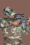 Soldato degli Stati Uniti Marine Corps del maschio che tende fucile di assalto M4 sopra fondo marrone Fotografia Stock Libera da Diritti