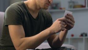 Soldato dell'esercito che esamina la foto dell'amica, moglie mancante, sensibilità romantiche, amore archivi video