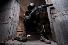 Soldato delle forze speciali che tende un fucile nella stanza scura Immagine Stock