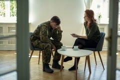 Soldato depresso ed il suo psicoterapeuta durante la sessione Vista attraverso una porta fotografia stock
