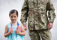 soldato e figlia con le bandiere di U.S.A., nella stanza concreta fotografia stock libera da diritti