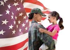 soldato e figlia davanti alla bandiera degli S.U.A. immagine stock