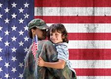 soldato e figlio davanti alla bandiera degli S.U.A. immagini stock