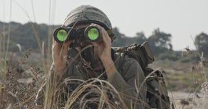 Soldato israeliano che striscia dalla copertura e che guarda tramite il binocolo archivi video