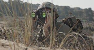 Soldato israeliano che striscia dalla copertura e che guarda tramite il binocolo video d archivio