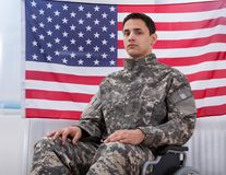 Soldato patriottico che si siede sulla sedia a rotelle contro la bandiera americana