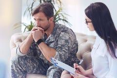 Soldato pensieroso che ricorda le memorie di guerra allo psicoterapeuta femminile Immagine Stock Libera da Diritti