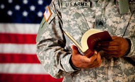 Soldato: Sfogliare una bibbia Fotografia Stock Libera da Diritti