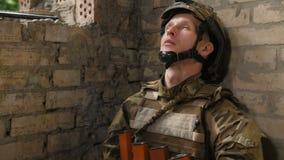 Soldato stanco dell'esercito che allevia sforzo con la sigaretta video d archivio