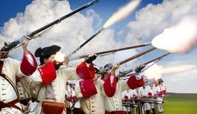 Soldats allumant leurs mousquets dans un champ de bataille Photos libres de droits
