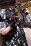Soldats dans les masques noirs visant avec des canons photographie stock
