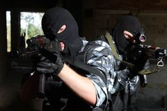 Soldats dans les masques orientant la cible avec des canons images stock