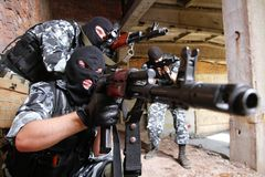 Soldats dans les masques orientant la cible avec des canons Images libres de droits