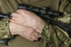 Soldats händer i kamouflage att rymma ett gevär royaltyfri bild