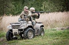 Soldats sur tout le véhicule de terrain - quadruple Photos stock